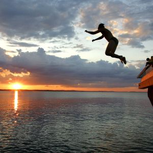 Ung man hoppar i havet