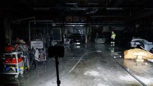 En bilverkstad där det brunnit är helt svart. En strålkastare lyser upp golvet och bilar.