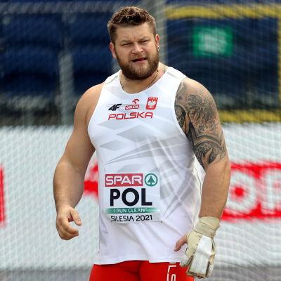 Pawel Fajdek är iklädd en vit tröja med texten POL på en tävlingslapp.