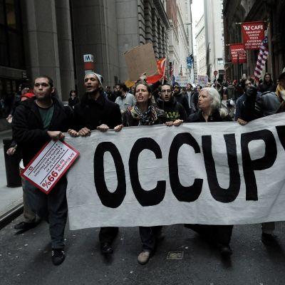 Occupy Wall Street -mielenosoittajat marssivat New Yorkin pörssin lähistöllä 17. marraskuuta 2011.