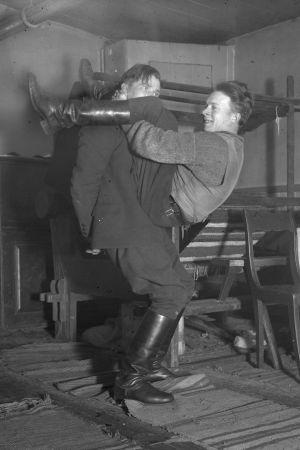 """Två män leker leken """"prova nacken"""", där den ena ska lyfta upp den ena med bara sin nackes styrka. Bilden är tagen 1935 i Bromarf."""