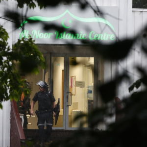 En kravallklädd polis går ut genom ingången till al-Noor Islamic Center i Bærum.