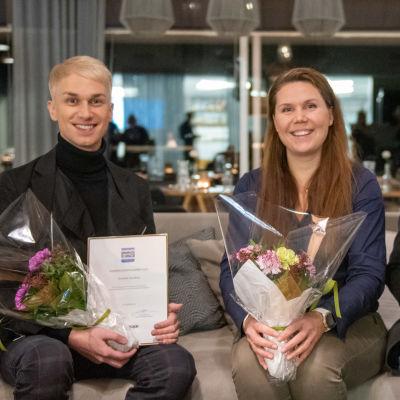 Christoffer Strandberg, Satu Österberg och Tom Gammals sitter i en soffa och håller i blommor och diplom.