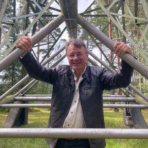 Stefan Blomqvist ler och tittar in i kameran. Han håller i stolparna på sitt vindkraftverk.