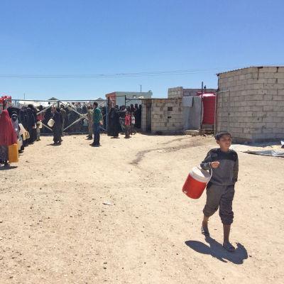 En pojke bär på ett ämbar. I bakgrunden kan man se kvinnor köa utanför en stängd port med vattenämbar i händerna.