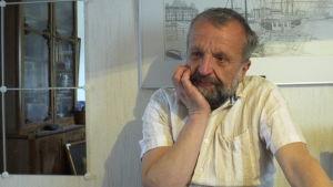 Henrik Othman lutar huvudet i handen vid köksbordet