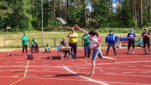 Urheilukentällä nainen heittää saapasta, ympärillä ihmisiä katsomassa, taustalla puita