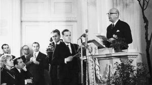 Kekkonen håller sitt uppmärksammade tal i universitetets aula den 12 mars 1964. Redaktör Eero Saarenheimo från Rundradion bandar