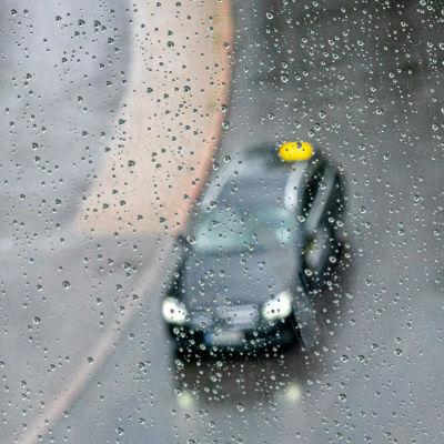 En taxi kör i regnet. Fågelperspektiv. Bilen syns genom ett regnvått fönster.