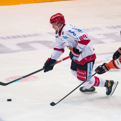 Patrik Karlkvist håller i pucken med en motståndare i ryggen.