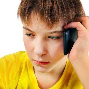 ledsen pojke pratar i telefon