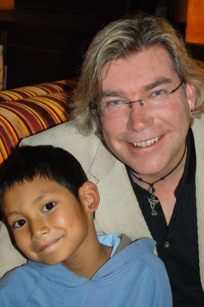 Mikael tillsammans med sin son i soffan. De ser båda rakt in i kameran.
