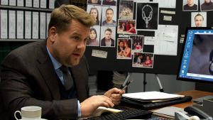 Närbild på John (James Corden) som sitter vid ett skrivbord.