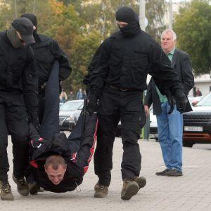 Belarusisk polis tar till krafttag mot protesterna och bär en demonstrant 27 september
