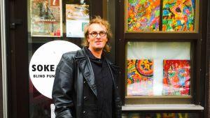 Andy Sundqvist och några av hans tavlor