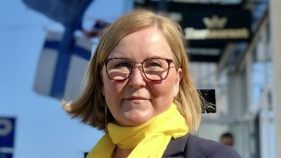 Kaisa Juuso med gul halsduk på Torneå-gata, med Finlands och EU-flagga i bakgrunden
