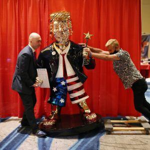 Två män reser upp en guldstaty på Donald Trump.