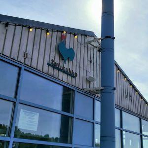 Kuva kahvila-ravintola Tulikukon julkisivusta. Ravintolan logo, vihreä kukko, näkyy kuvassa. Taustalla sininen taivas.