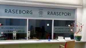 En kundbetjäning där personalen ska finnas bakom ett glas med texten Raseborg Raasepori på glaset. Stolar och litet datorbord syns framför disken. Inga människor på plats.