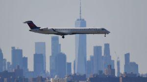 Ett flygplan går in för landning på JFK-flygfältet. I bakgrunden New Yorks disiga skyline