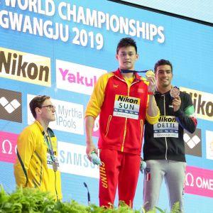Mack Horton står bakom podiet, när Sun Yang och Gabriele Detti poserar med sina medaljer.