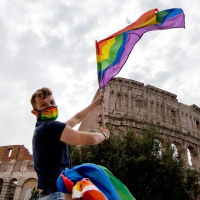 En man sitter på ett biltak och håller i en prideflagga. I bakgrunden romska colosseum.