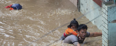 Vuxen bär barn genom en flod.