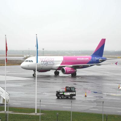 Wizz airs flyg i vitt, rosa och blått på landningsbanan.