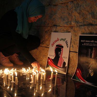 Jordanialainen nainen sytytti kynttilän terroristijärjestö Isisin murhaaman lentäjän muistoksi Ammanissa helmikuussa 2015.