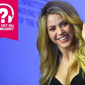 Shakira ler och vinkar mot kameran.
