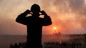 Soldat i ljuset av eldgivning i Gaza