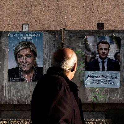 Äldre man tittar på valplakat för Marine Le Pen och Emmanuel Macron.