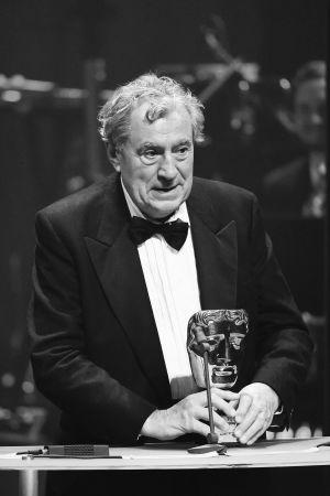 Svertvit bild av Terry Jones i en talarstol med ett pris i handen.