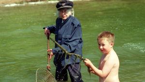 En pojke och en kvinna i kaptenuniform på en strand.