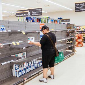 En man står vid en butikshylla som är så gott som tom.