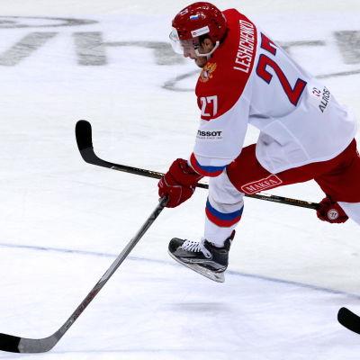 Vitklädd rysk ishockeyspelare rymmer undan med pucken från en tjeckisk motspelare