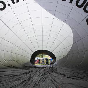 Ihmiset katselevat kuumailmapallon kuoren suulla ylöspäin maassa olevan pallon sisälle.