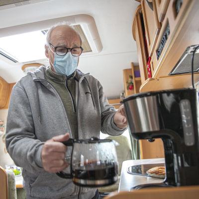 Erkki Helin ottaa kahvipannun pois kahvinkeittimestä.