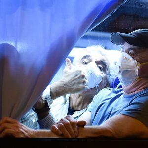 Två män med andningsskydd ler och tittar ut ur ett bussfönster. Ena mannen visar tummen upp.