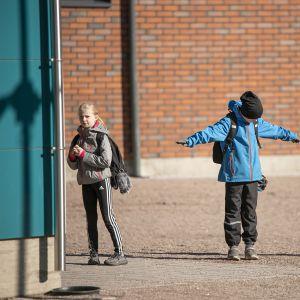 Oppilas varmisti, että onhan opettajan aiemmin ohjeistama turvaväli varmasti riittävä. Kouluun päästettiin sisälle kerrallaan muutama oppilas.