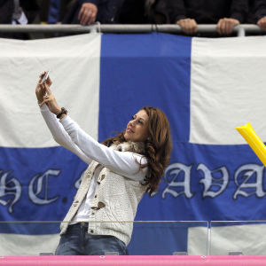 Kvinna tar selfie framför finska flaggan, Rumänien-Finland, oktober 2015.