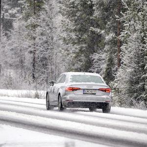 Auto ajaa lumisella tiellä Kolarissa.