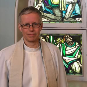Prästen Rose-Maj Friman klädd i vit alba står framför fönster med glaskonst i Brändö kyrka i Vasa.