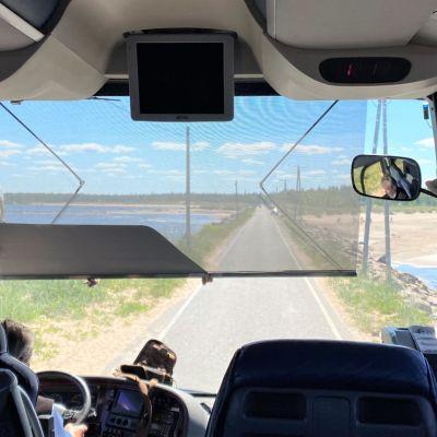 Mikko Kallioinen ajaa bussia Ohtakarin maisemissa Lohtajalla. Meri näkyy molemmin puolin tietä.