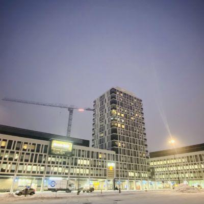 Kuopion vuonna 2021 valmistuneen matkakeskuksen uudet rakennukset ja tilat talvella valaistuna iltahämärässä.