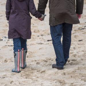 Man och kvinna går på stranden, håller varandra i handen