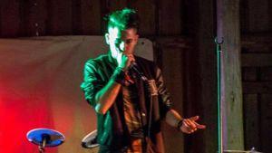 En ung man står på en scen med mikrofon i handen. I bagrunden syns instrument och en robust trävägg.