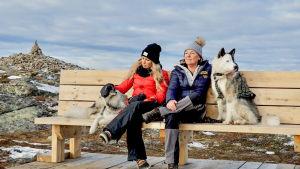 Krista och Lotta och två hundar sitter på en bänk och njuter av naturen.