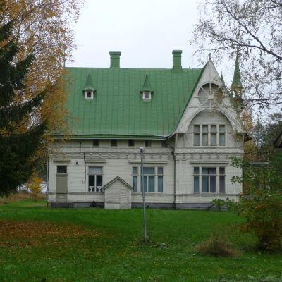 En gammal sommarvilla i tre våningar. Vit fasad med högt grönt plåttak. I förgrunden träd i höstskrud.