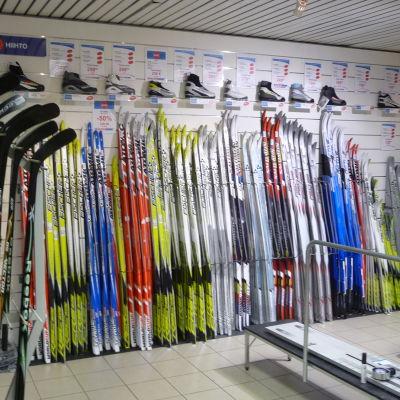 skidor och hockeyklubbor står uppradade i en sportaffär